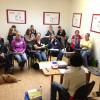 Eine Gruppe von Seminarteilnehmern sitzt an einem Vortrag und hört gespannt zu.